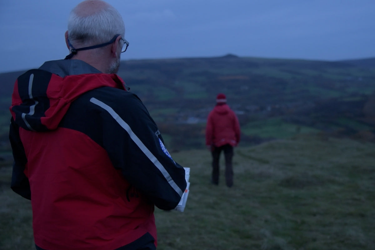 Two members of Edale Mountain Rescue Team demonstrating the leapfrogging navigation technique