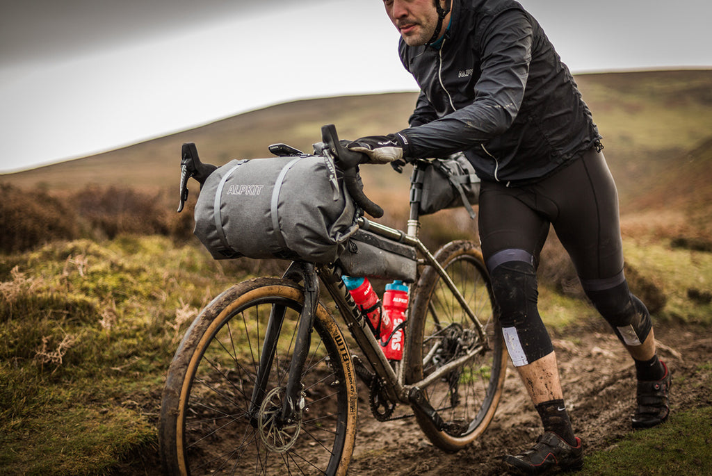 A man pushing his bikepacking bike through the mud on a wet day in the hills