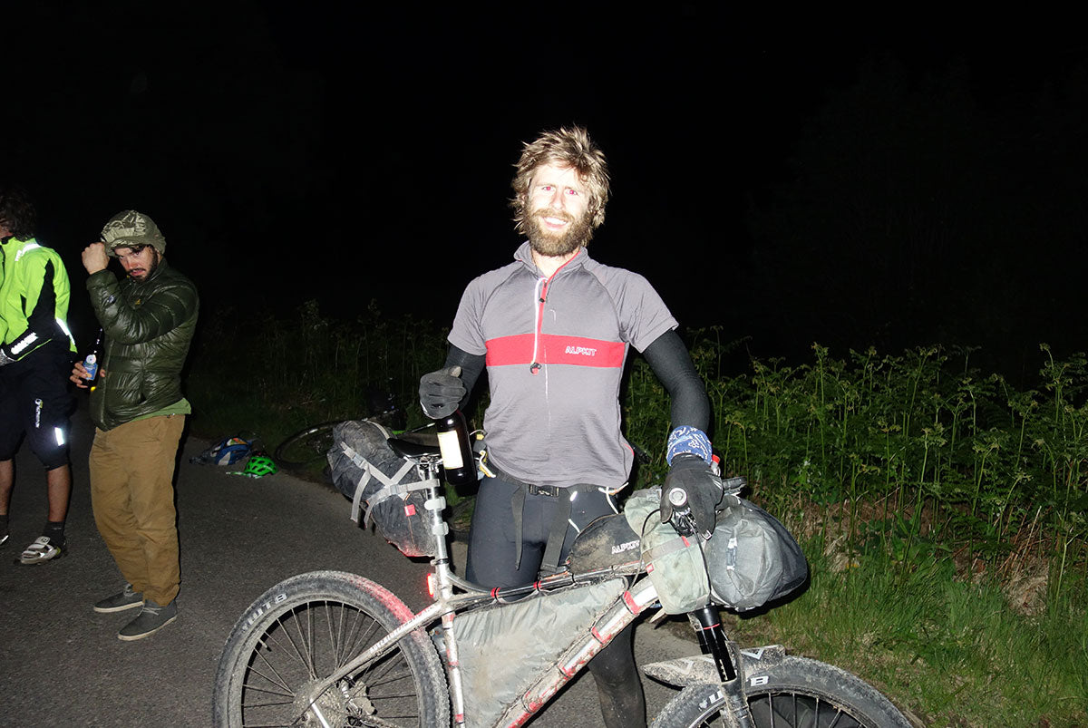 Pete at the finish line at night, his bike in one hand, and a bottle of wine in the other