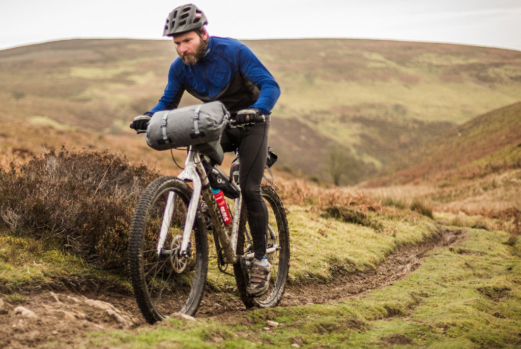 A man riding his rigid bikepacking bike through the mud on a wet day in the hills