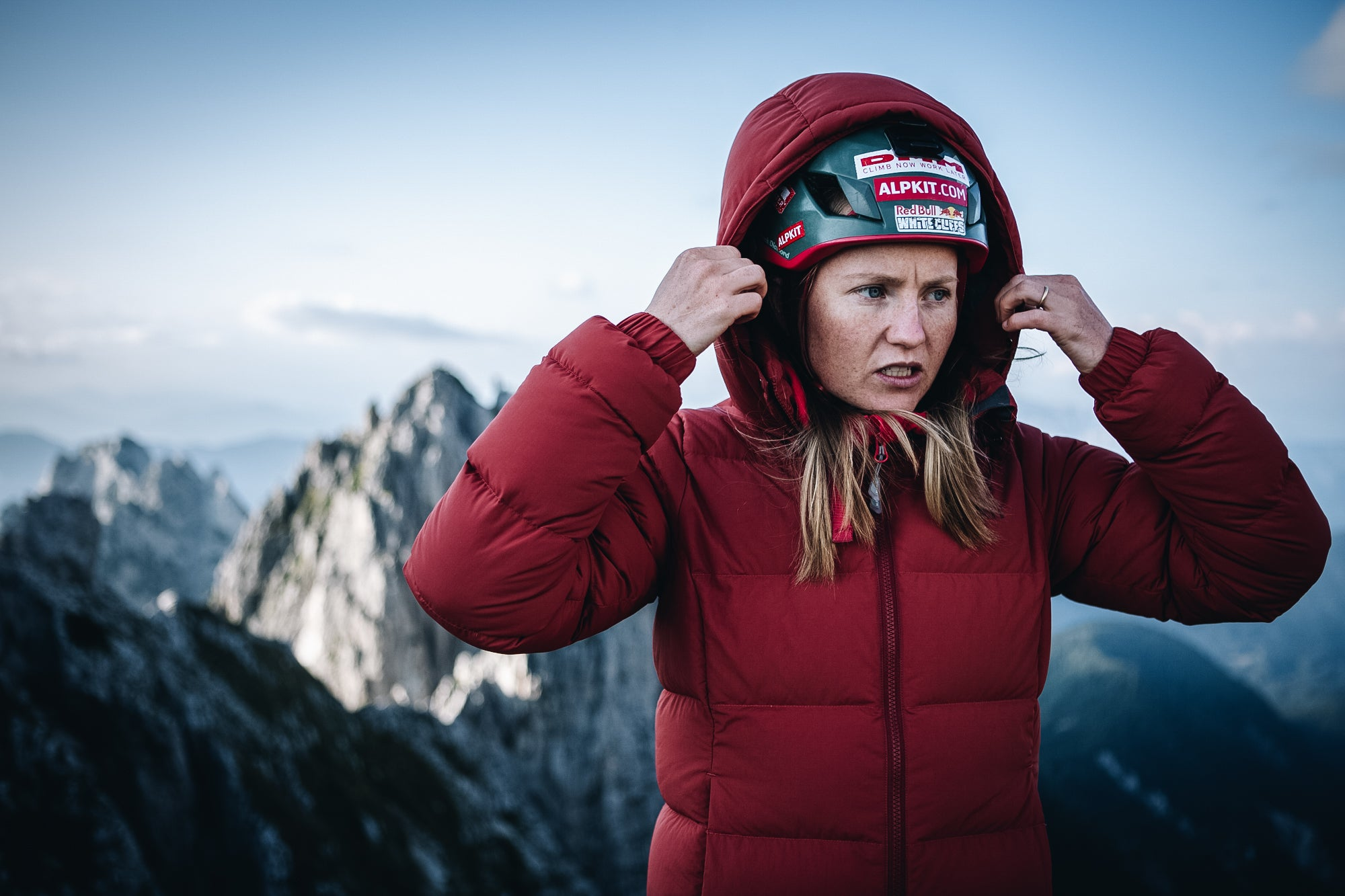 A woman wearing the Filo down jacket with the hood up over a climbing helmet in the Slovenian Alps