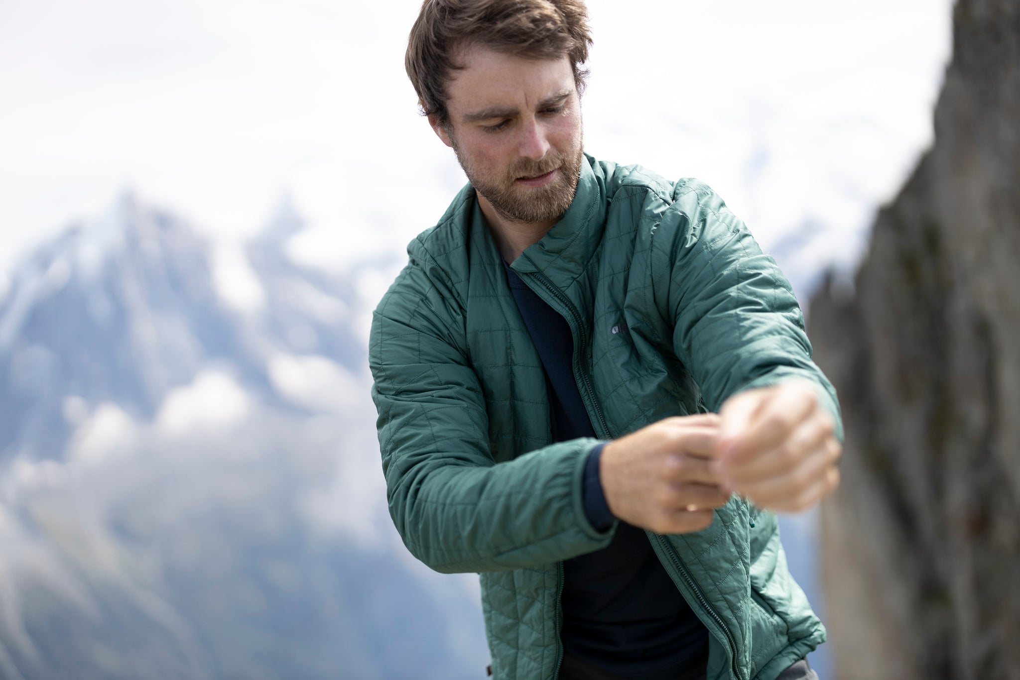 A man pulling on the Heiko Primaloft lightweight insulated jacket with quilted baffles