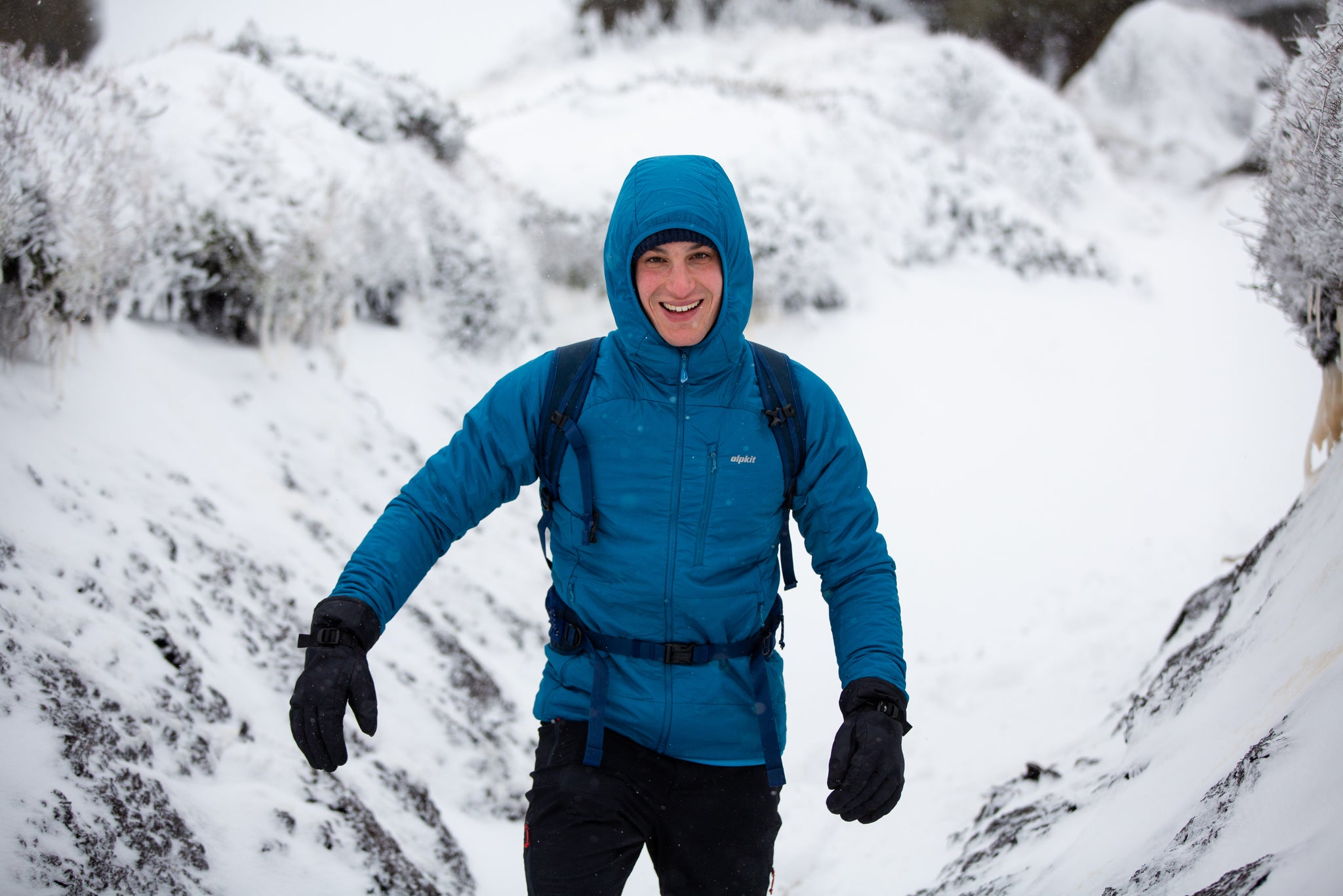 A man walking in the snow on Kinder Scout in the Peak District wearing a Primaloft Gold Active breathable insulated jacket