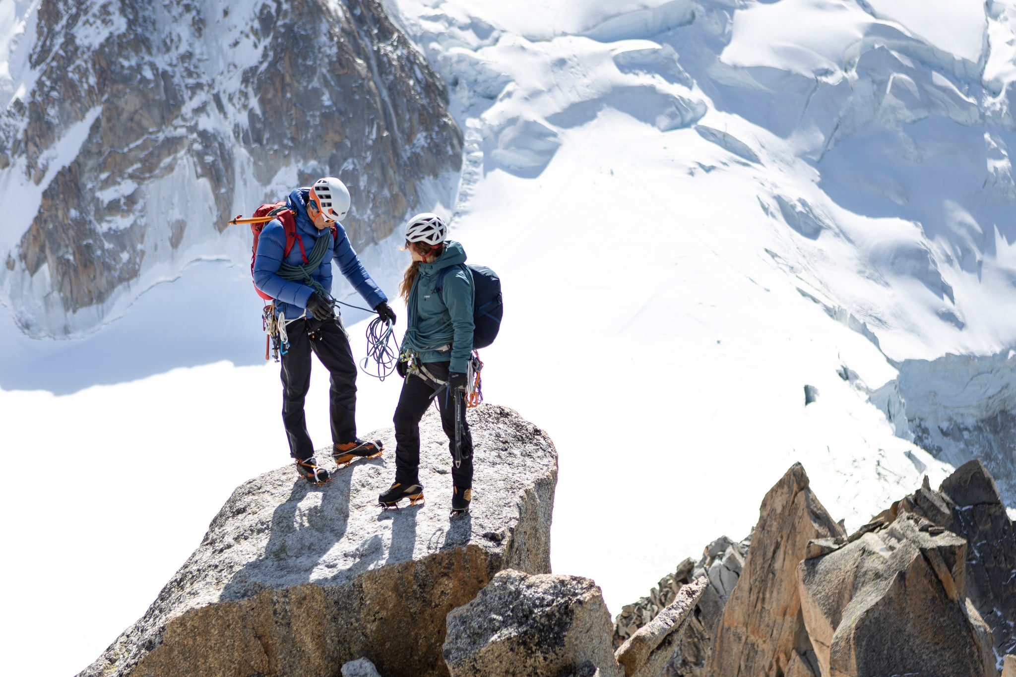 Two people standing on a platform in the French Alps wearing the Fantom Down Jacket and the 0Hiro Primaloft Jacket
