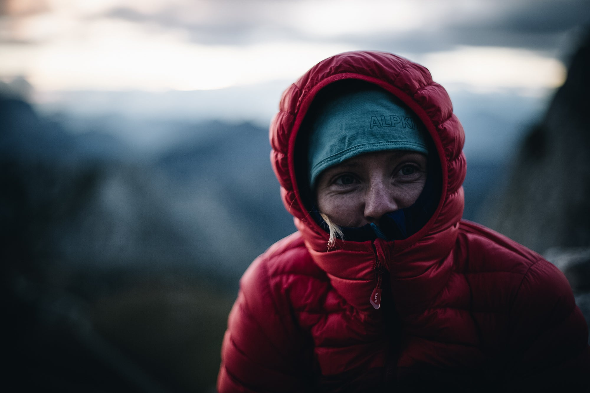 A woman hunkering down in her Filoment down jacket in the Slovenian Alps with the hood up