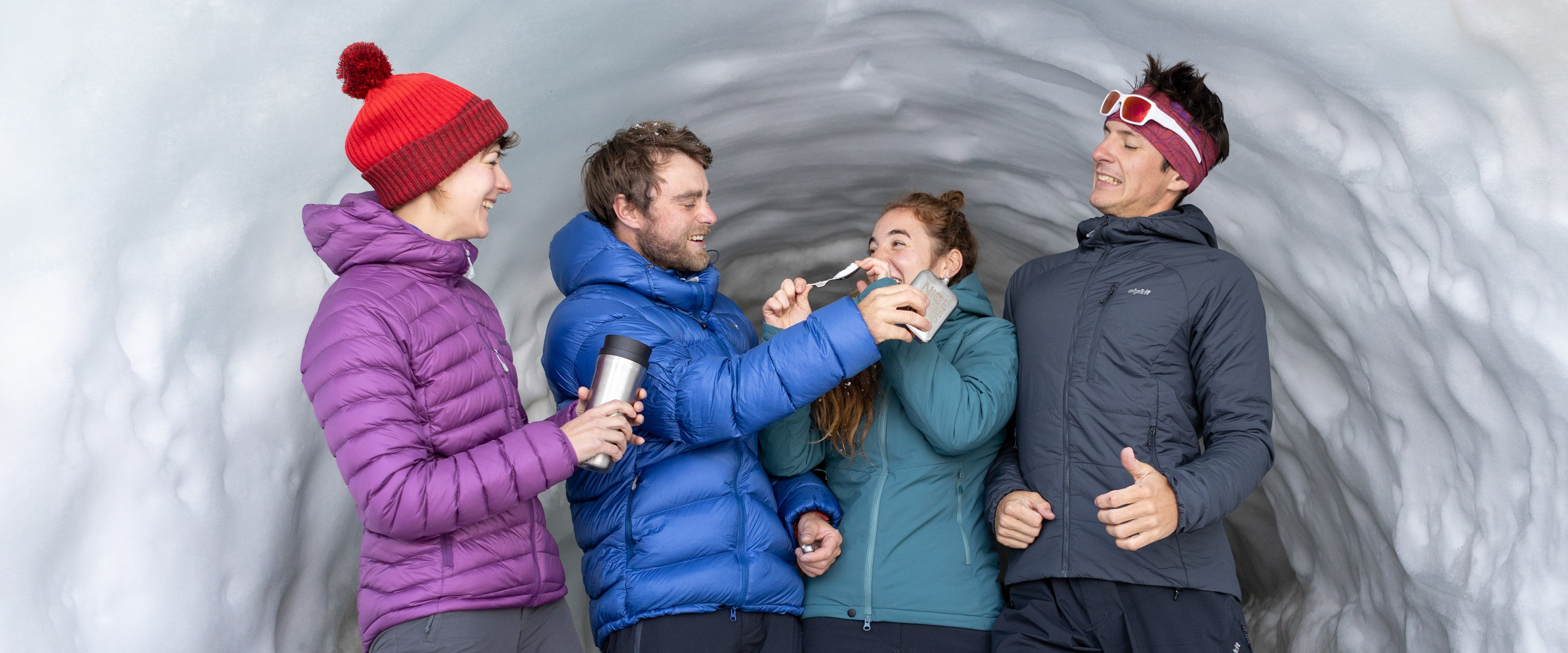 Four people wearing down jackets and Primaloft synthetic insulated jackets in an ice cave in Chamonix