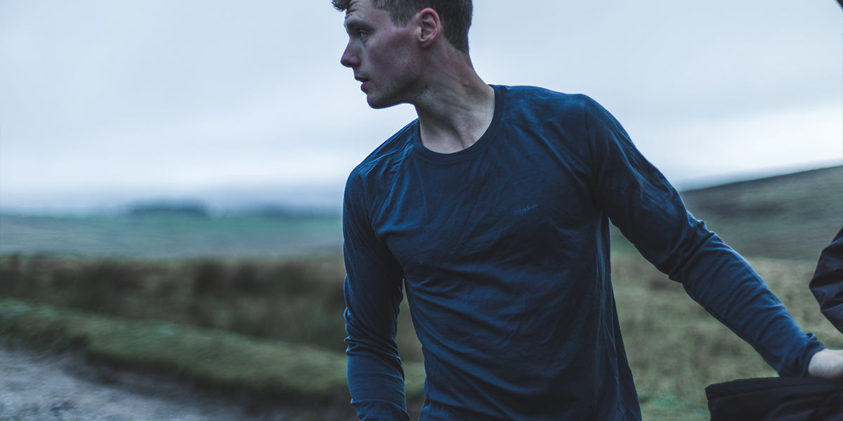A man wearing a merino top about to get changed after a run