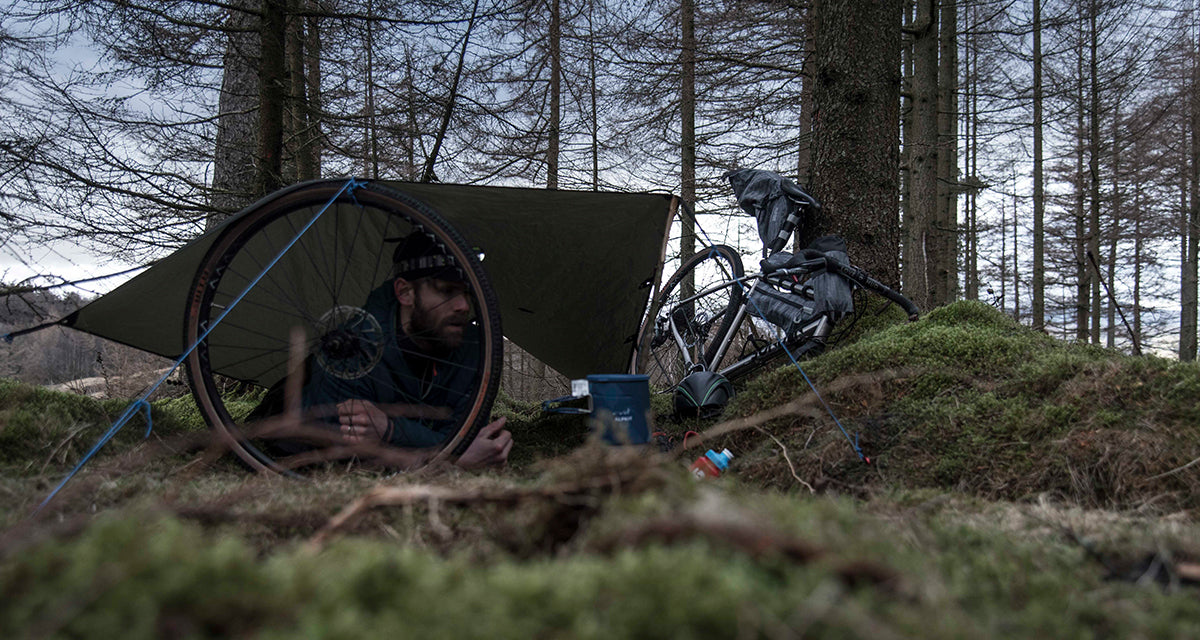 A man using his bike wheel to hold up his tarp shelter in the forest