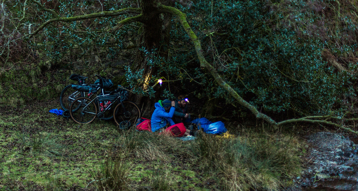 two men getting into bivvy bags at dusk, in the forest with their bikes behind them