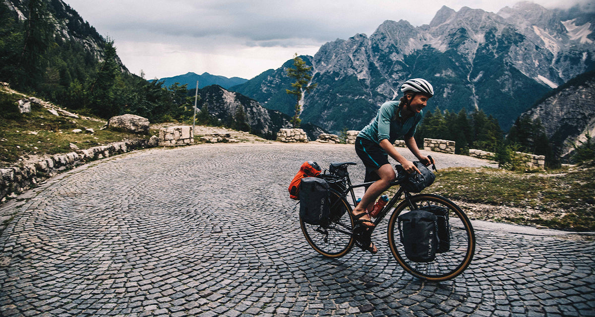 A woman cycling up a hill in Slovenia with cycle touring pannier bags attached