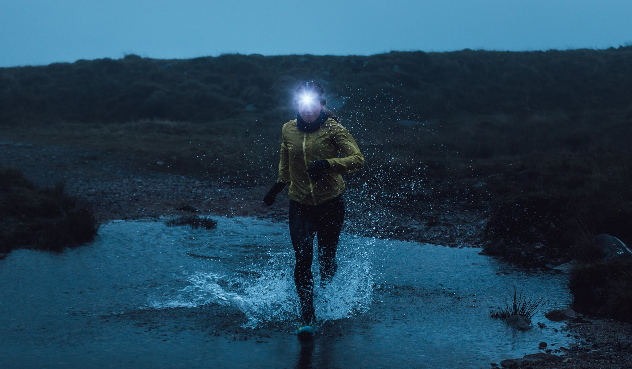 A woman trail running on Dartmoor with a running head torch