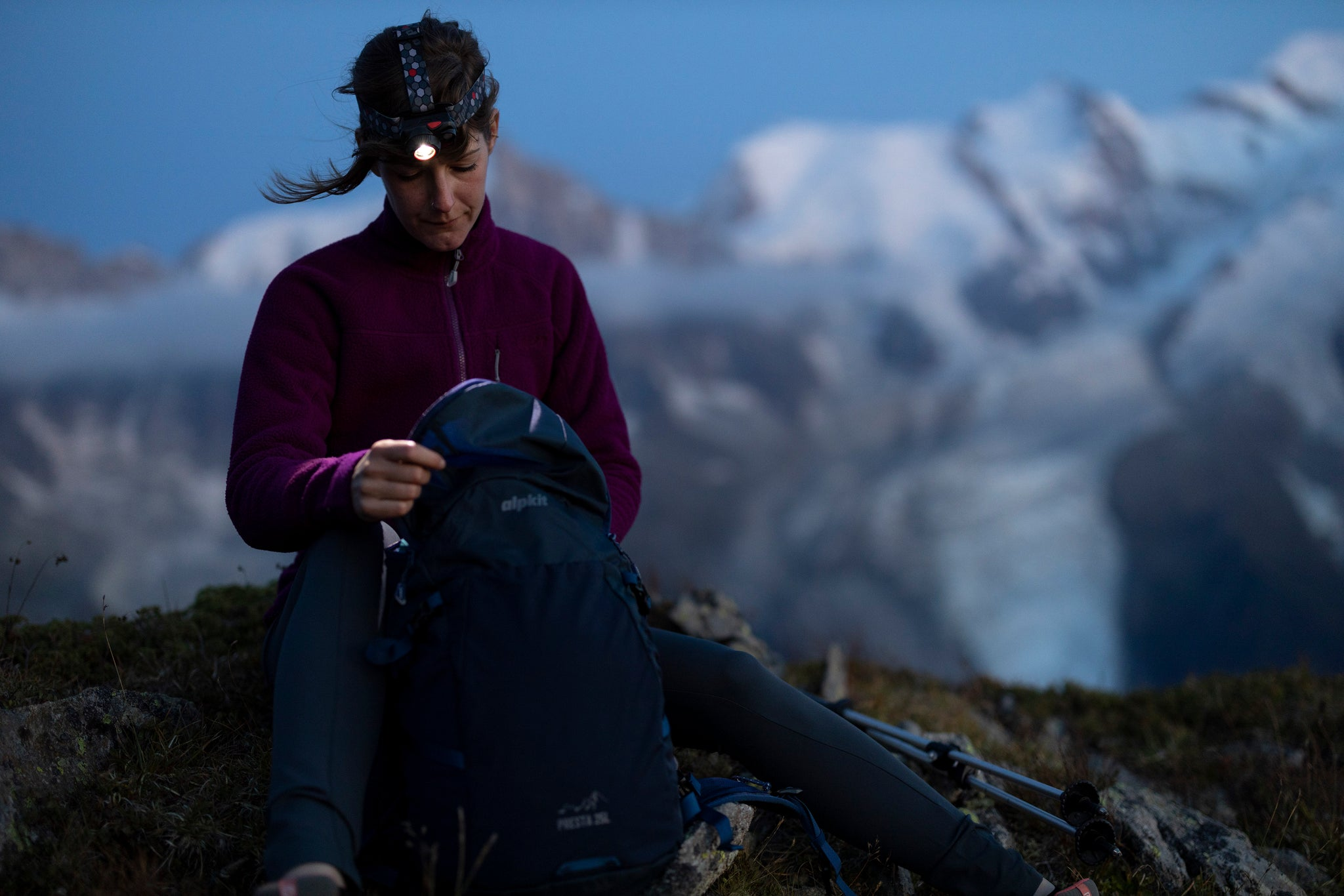 A woman looking inside her rucksack with a rechargeable head torch in the French Alps