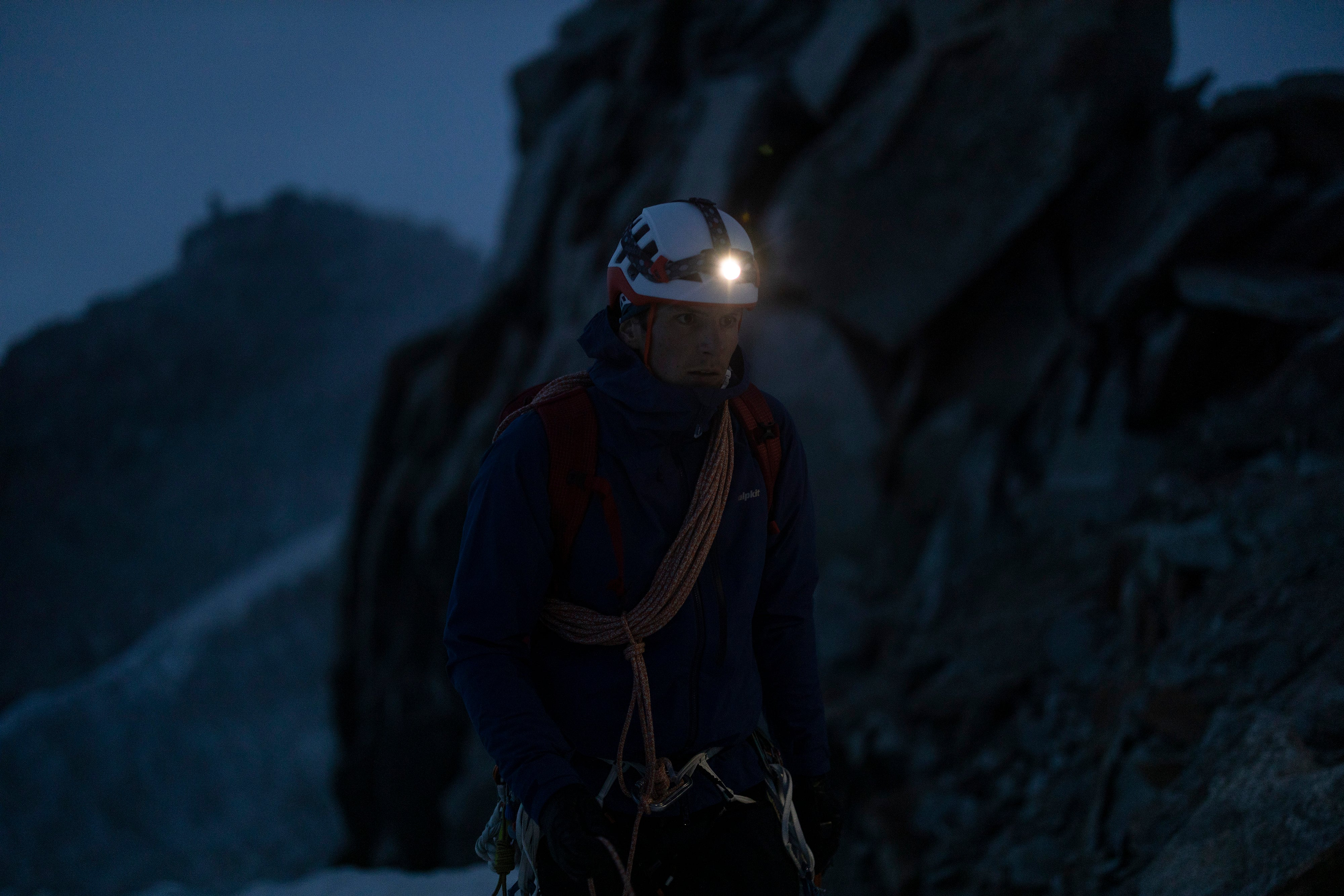 A man with a headtorch strapped over his climbing helmet
