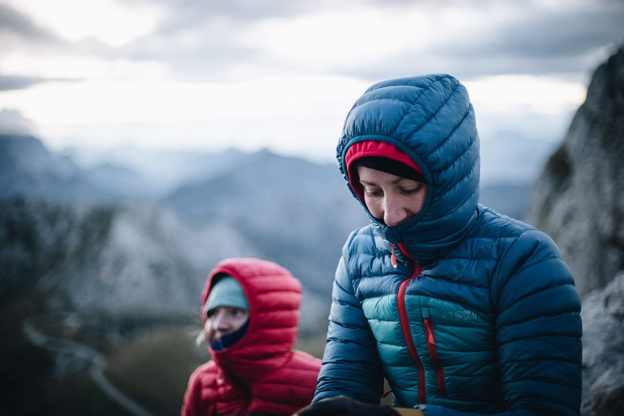 Two people sitting in the Slovenian Alps in ultralight Filament down jackets with the hoods up
