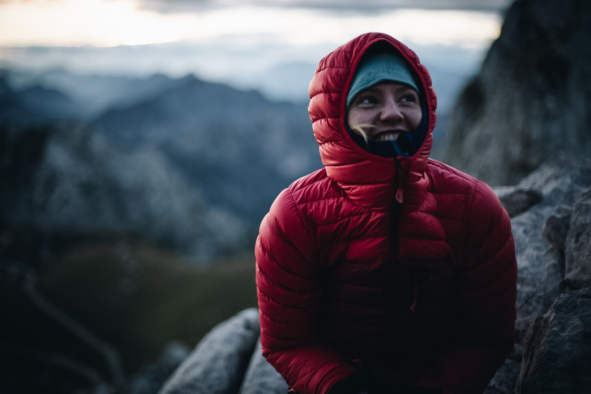 A woman wearing a Filament down jacket with the hood up in the Slovenian Alps