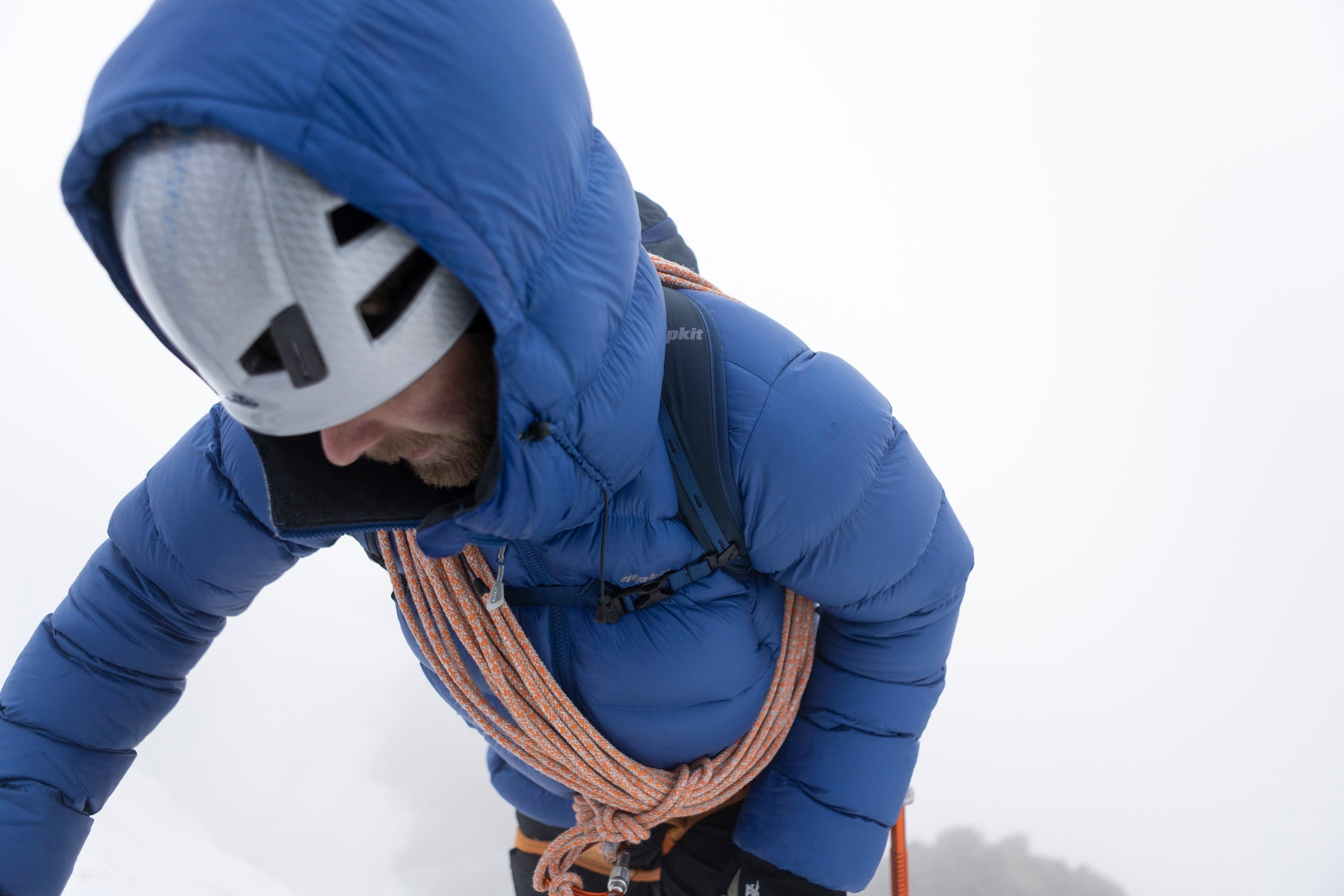 A man struggling up a steep slope in the snow wearing the Fantom hydrophobic down jacket with ethically sourced goose down
