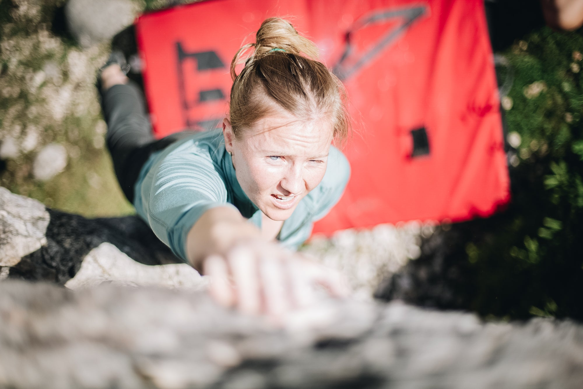 Woman bouldering in Slovenia in a merino wool long-sleeved t-shirt