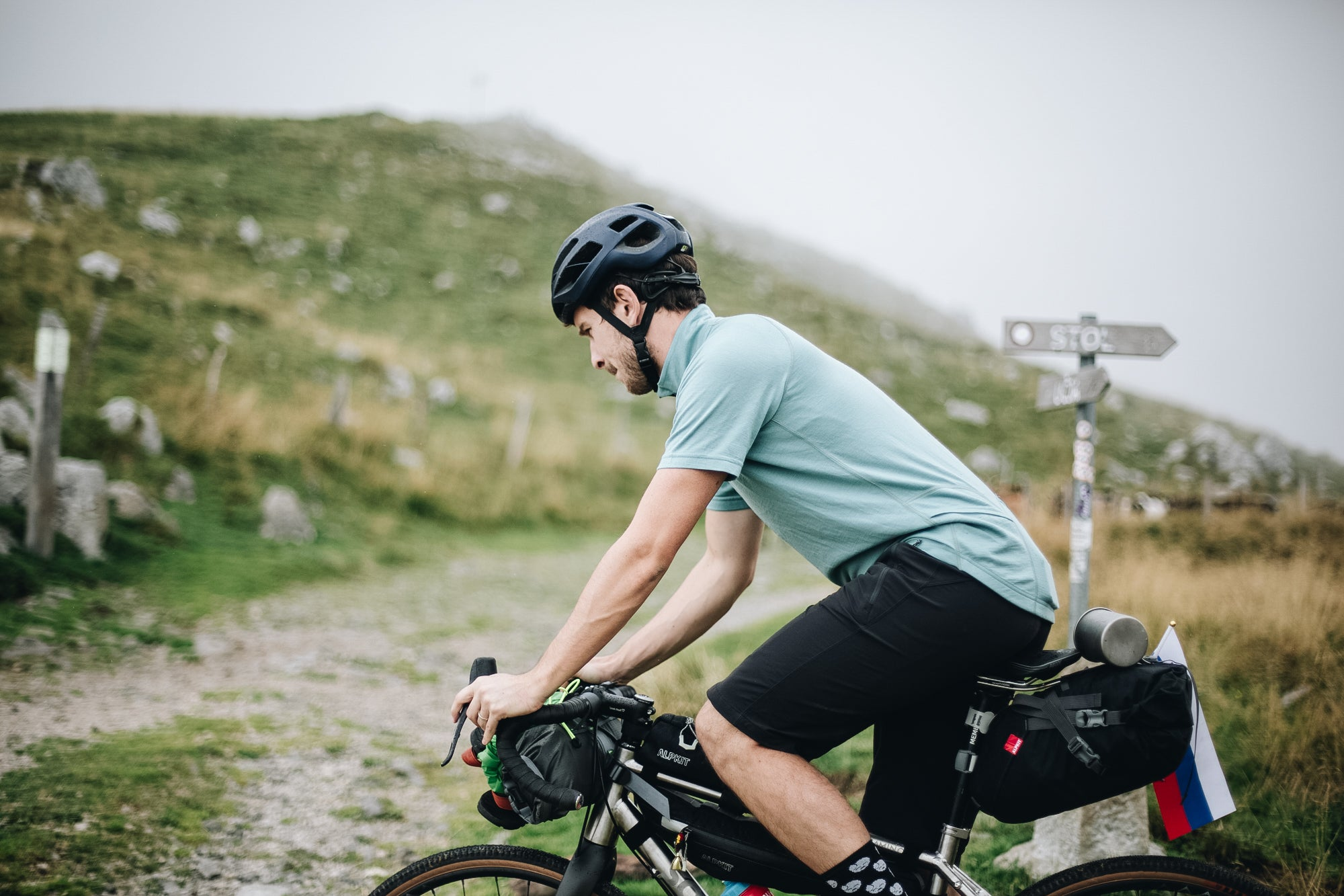 Man cycle touring on a gravel track in Slovenia, wearing a merino wool cycling jersey