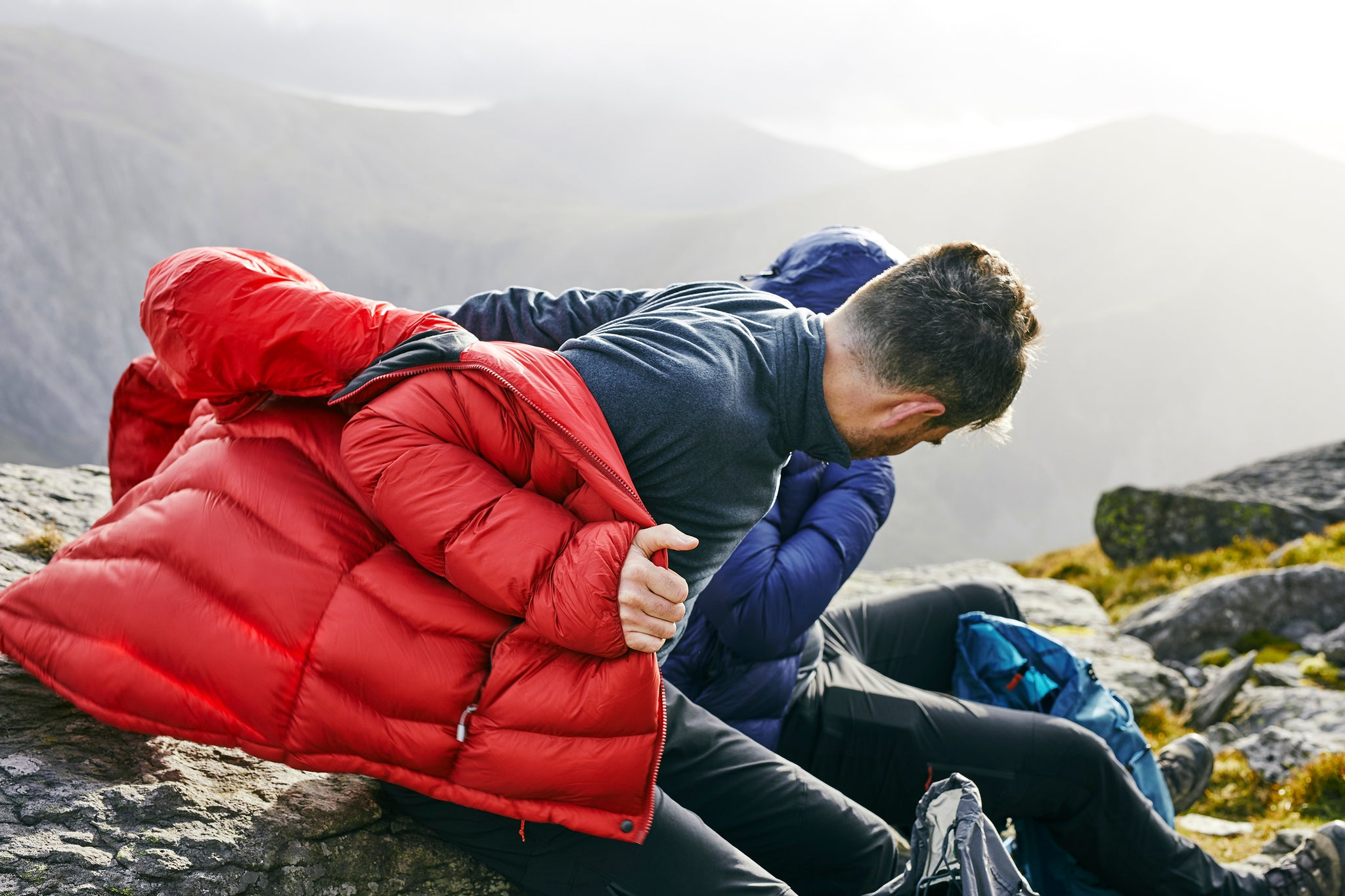 Pulling on the Fantom down jacket in Snowdonia