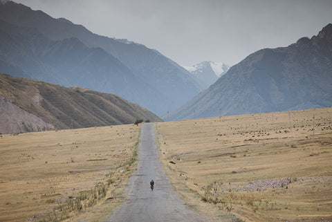 A man in the middle of the mountains riding his bike