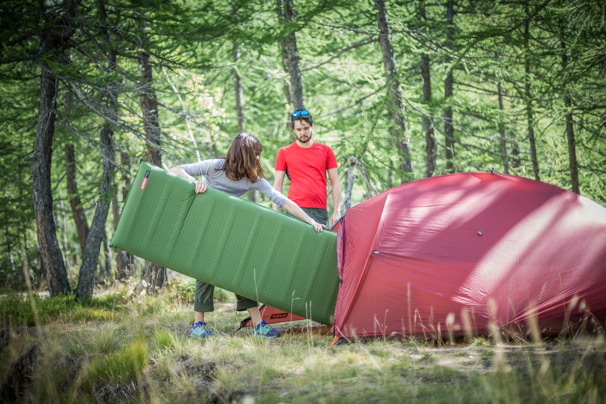 Putting a Dozer camping mat into a tent in a wooded area in Chamonix