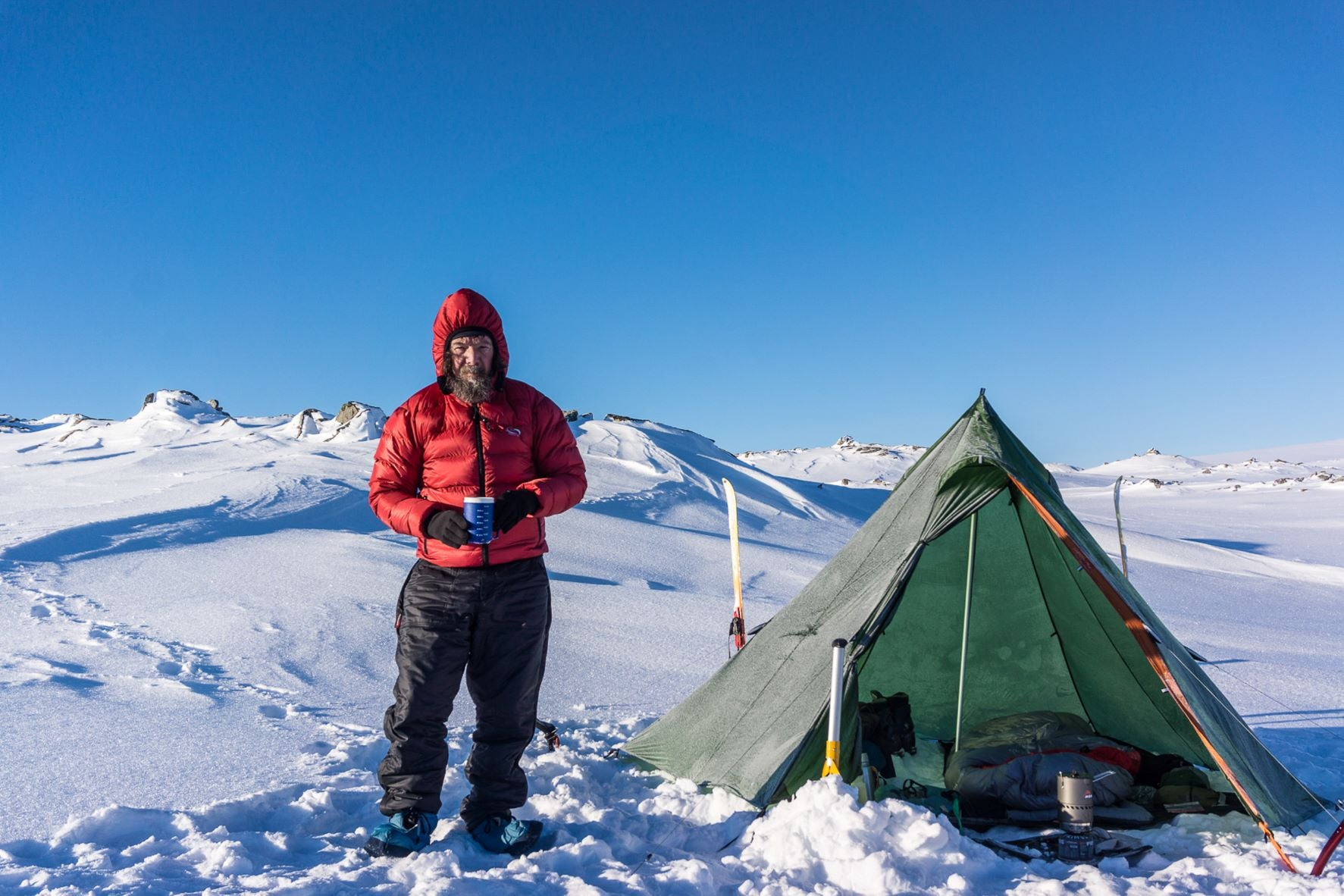 Townsend stands next to tent in snow