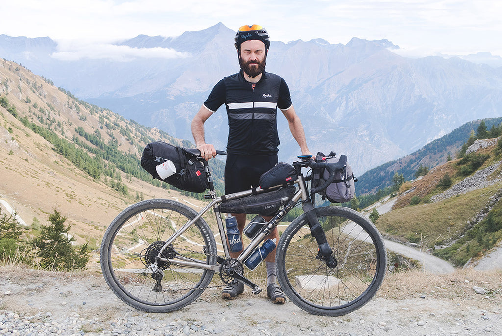 A man holding his sonder camino ti loaded up with bikepacking bags on a gravel path in the mountains