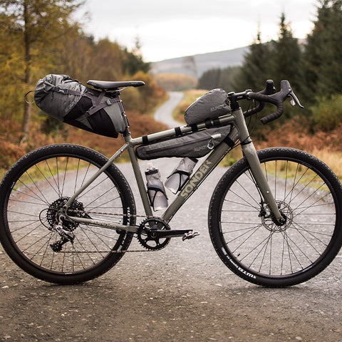A grey Sonder Camino Al packed up with bikepacking bags on a gravel track