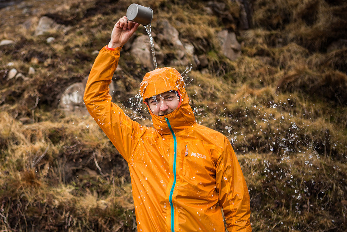 A man in a waterproof jacket pouring a cup of water on his head