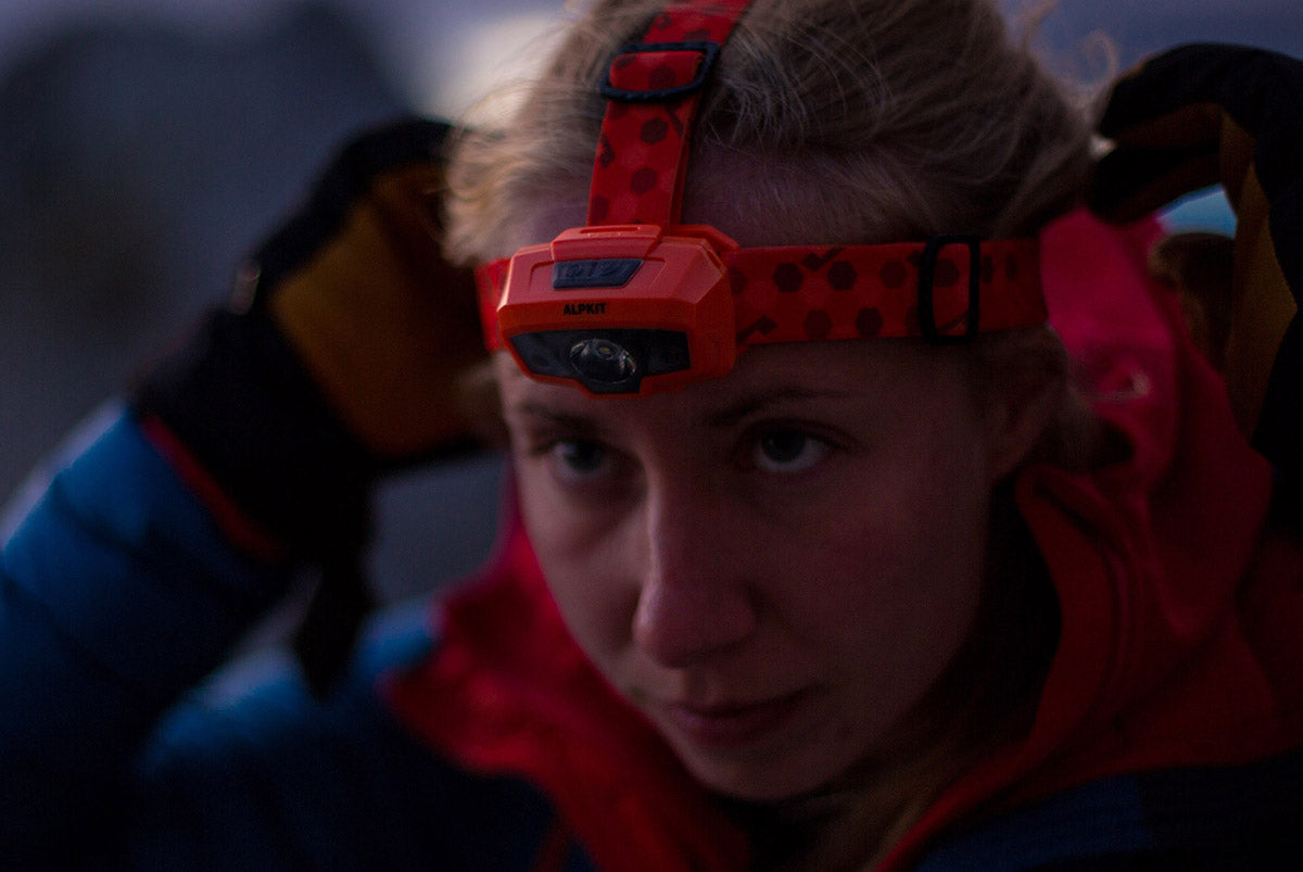 Mountaineer Anna Wells adjusting the Alpkit head torch in Slovenia