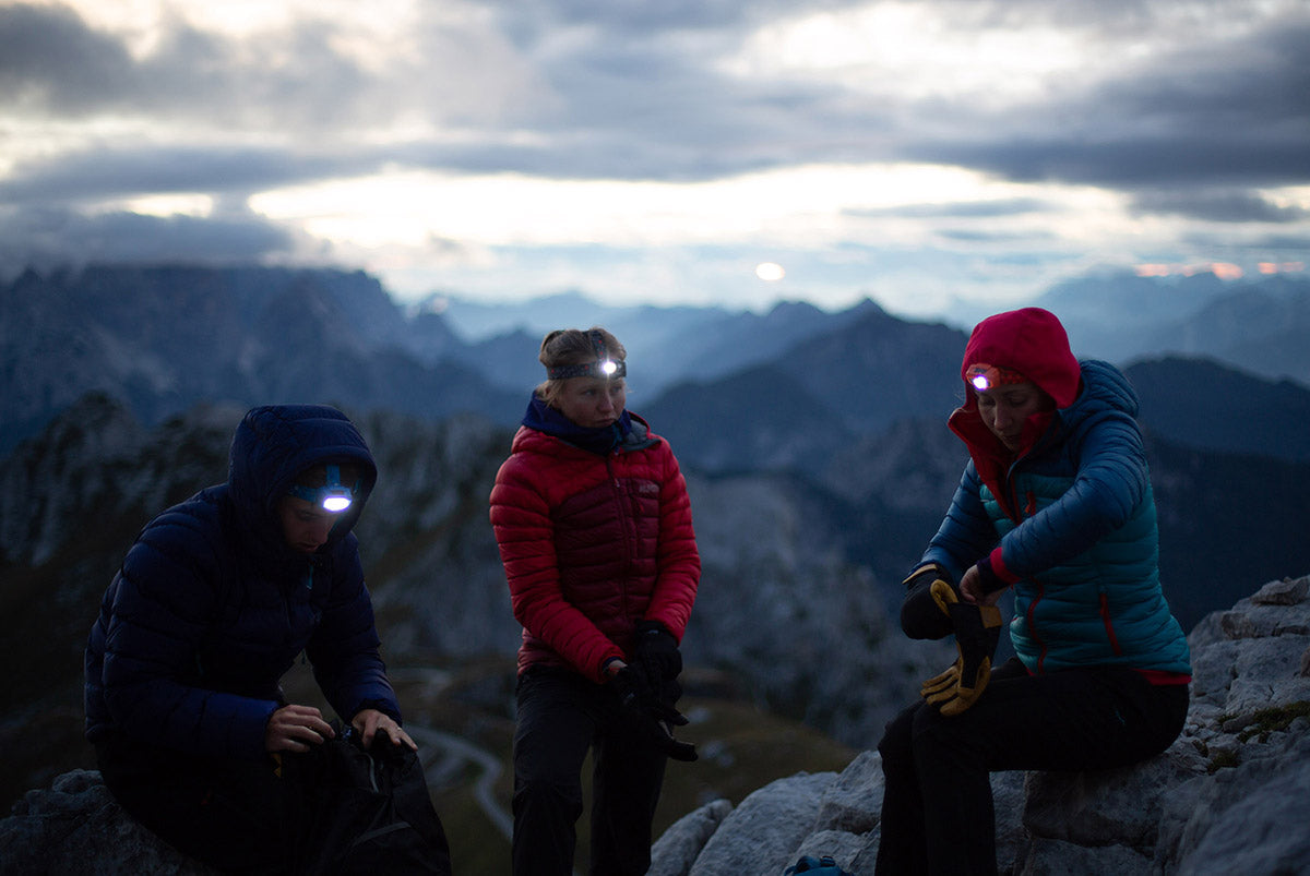 Group of three hikers in down jackets wearing head torches at twilight in the Slovenian mountains