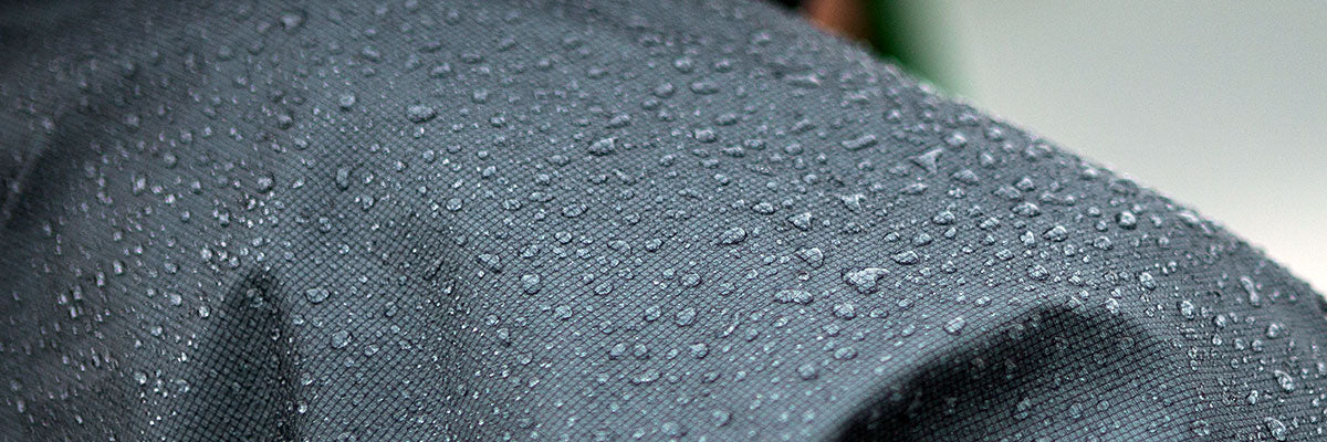 Water beading up into droplets on the surface of a waterproof fabric