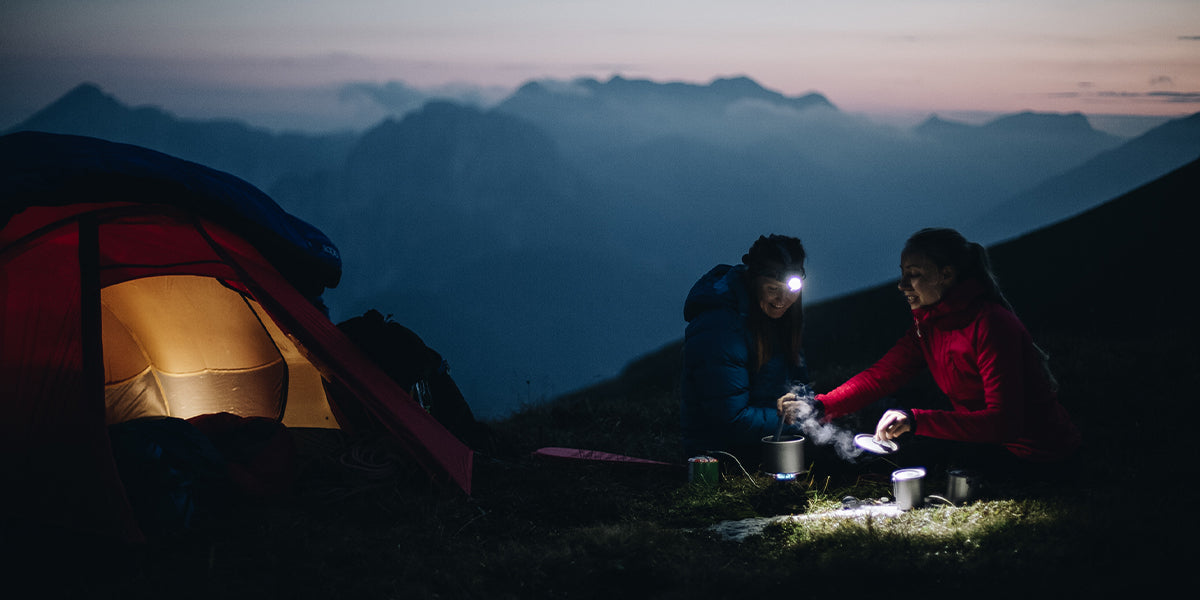 Two women cooking dinner next to their tent at dusk in the Slovenian mountains