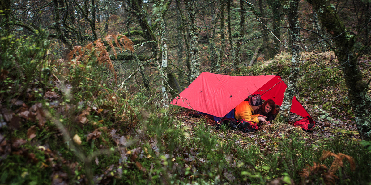two people camping underneath a red tarp in the woods