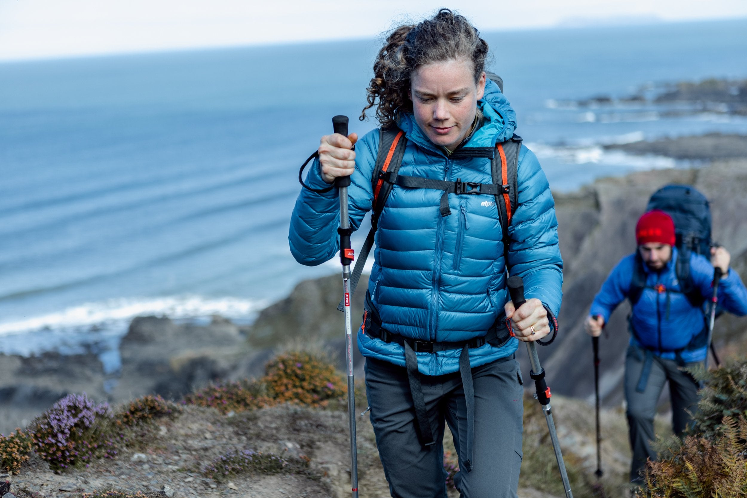 A woman walking in the Filoment lightweight down jacket with recycled down and recycled fabrics on the Devon coast
