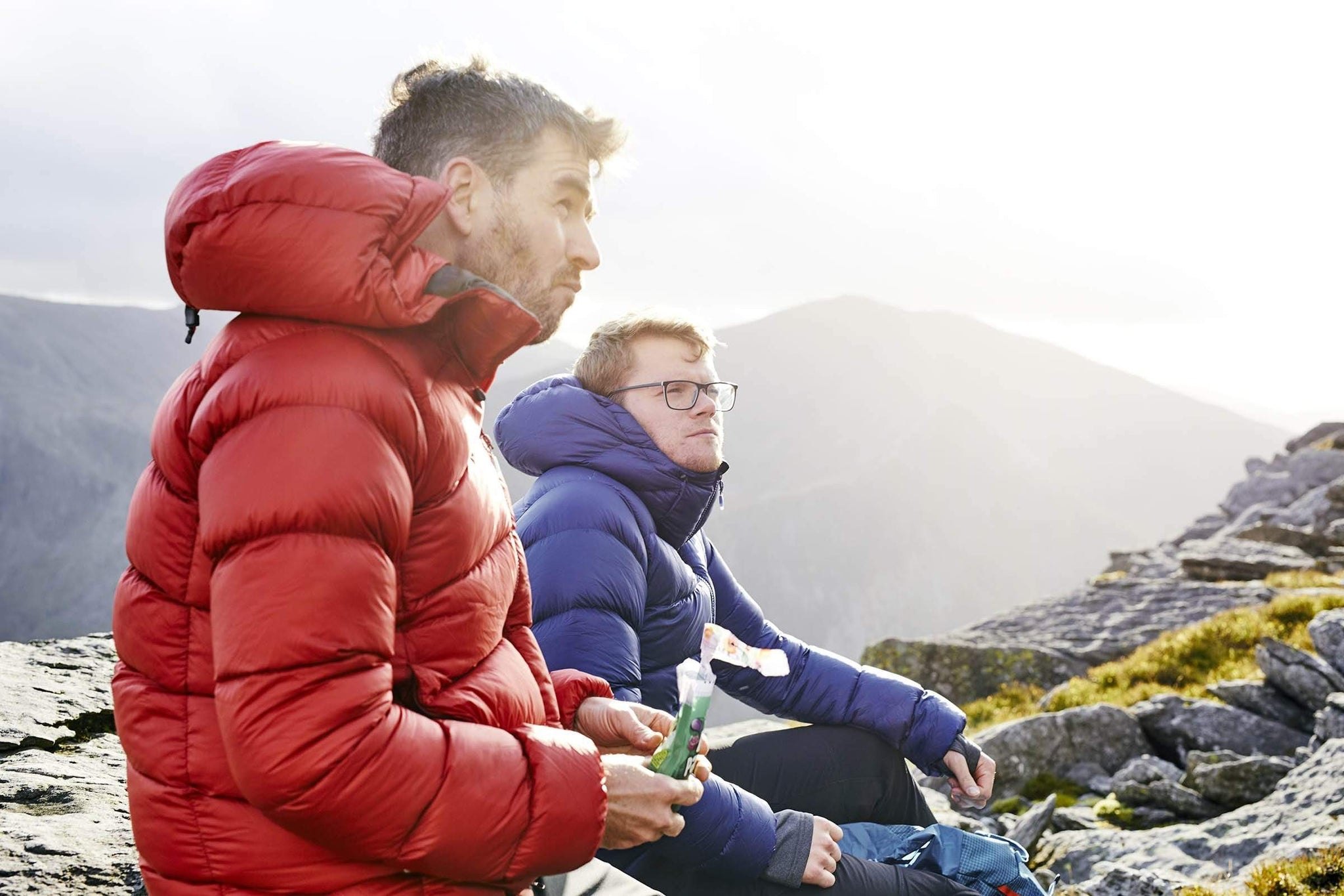 Two men sitting on top of a mountain in Snowdonia in the Fantom down jacket