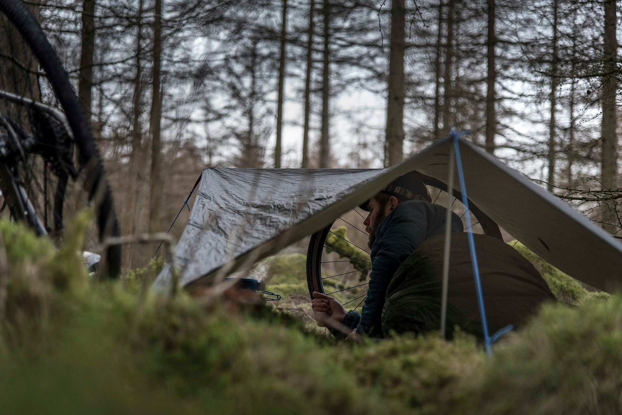 Man sleeping in a sleeping bag, in a bivvy bag, under a tarp, whilst bikepacking