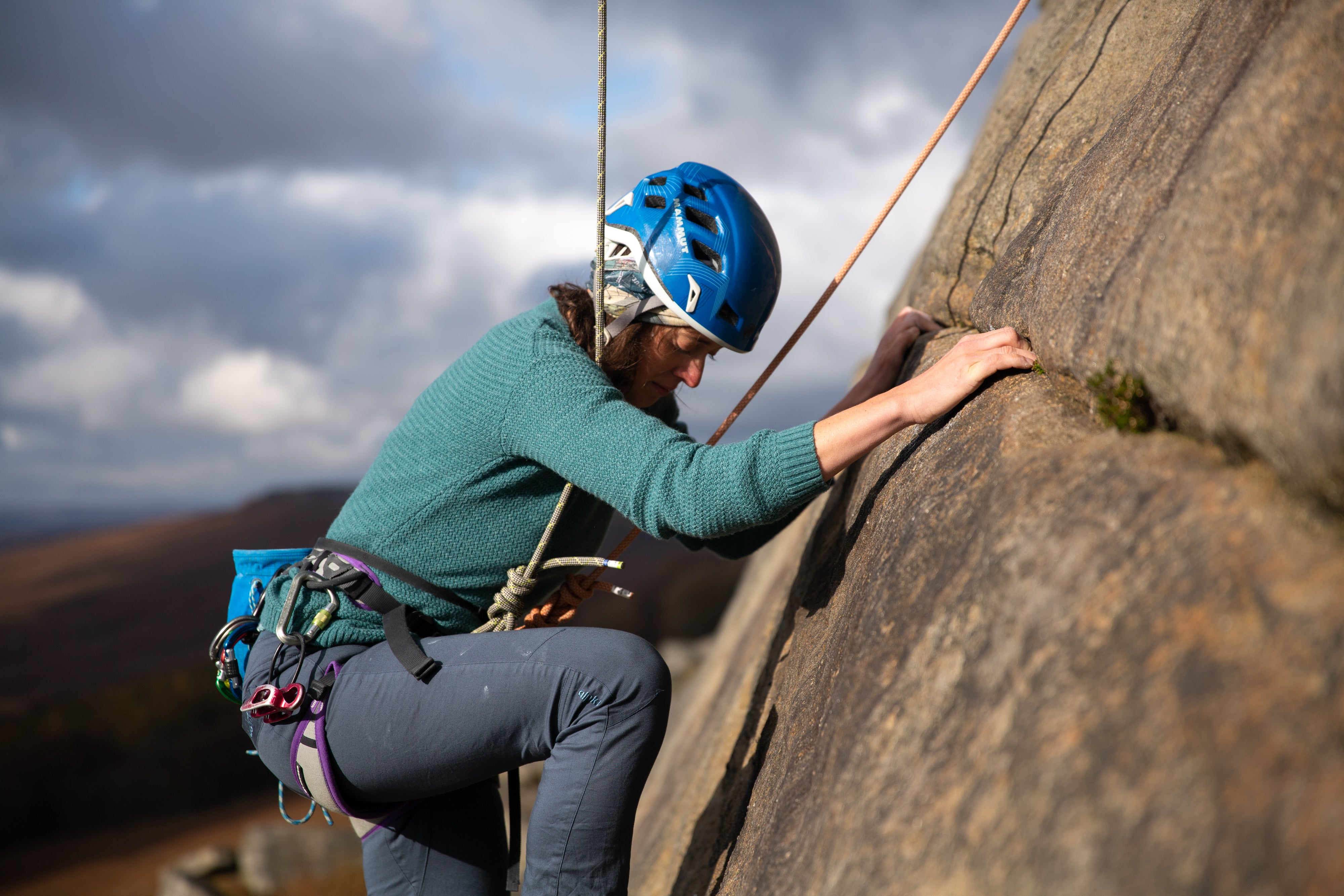 A woman trad climbing on Stanage Edge in the Peak District