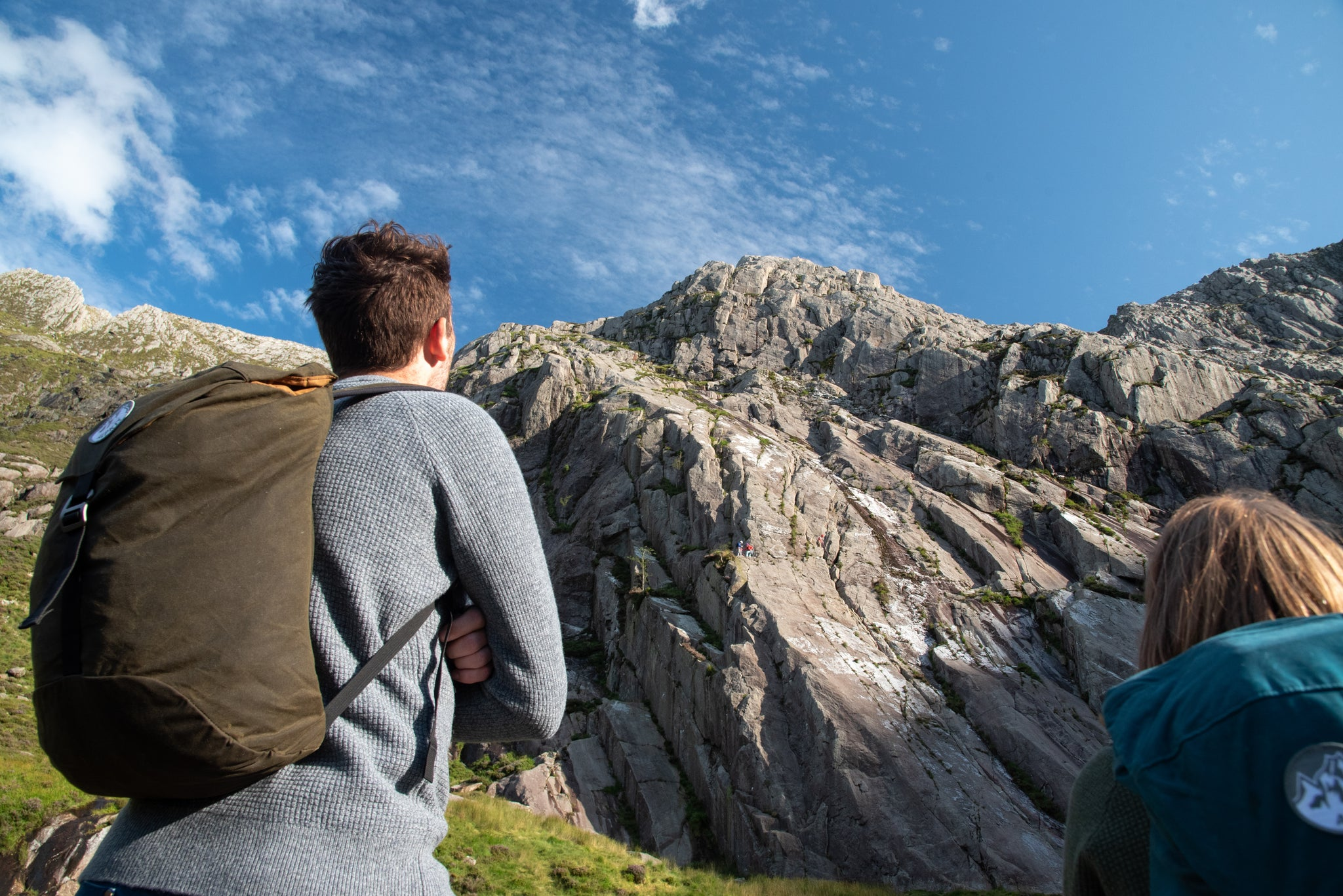 A man and a woman watching climbers on Tryfan in Eryri / Snowdonia National Park