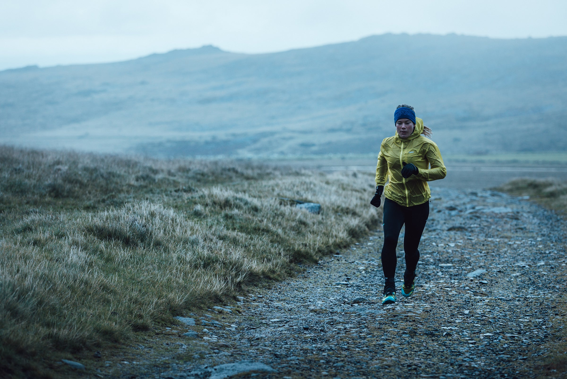 A woman in a yellow jacket running on a gravel path with hills in the background