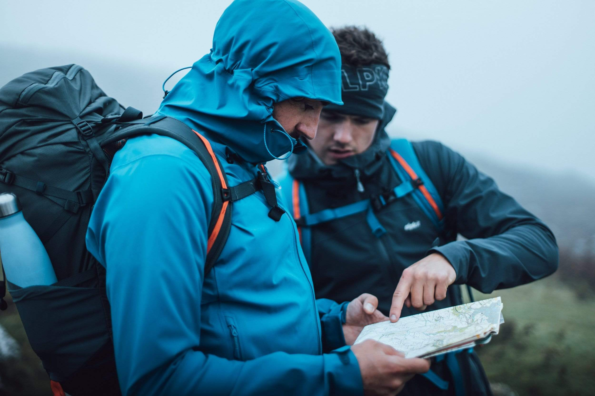 Two men navigating with a map and compass on Dartmoor in PFC-free waterproof jackets