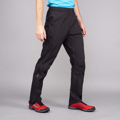 A man wearing black Parallax lightweight waterproof trousers on a grey background