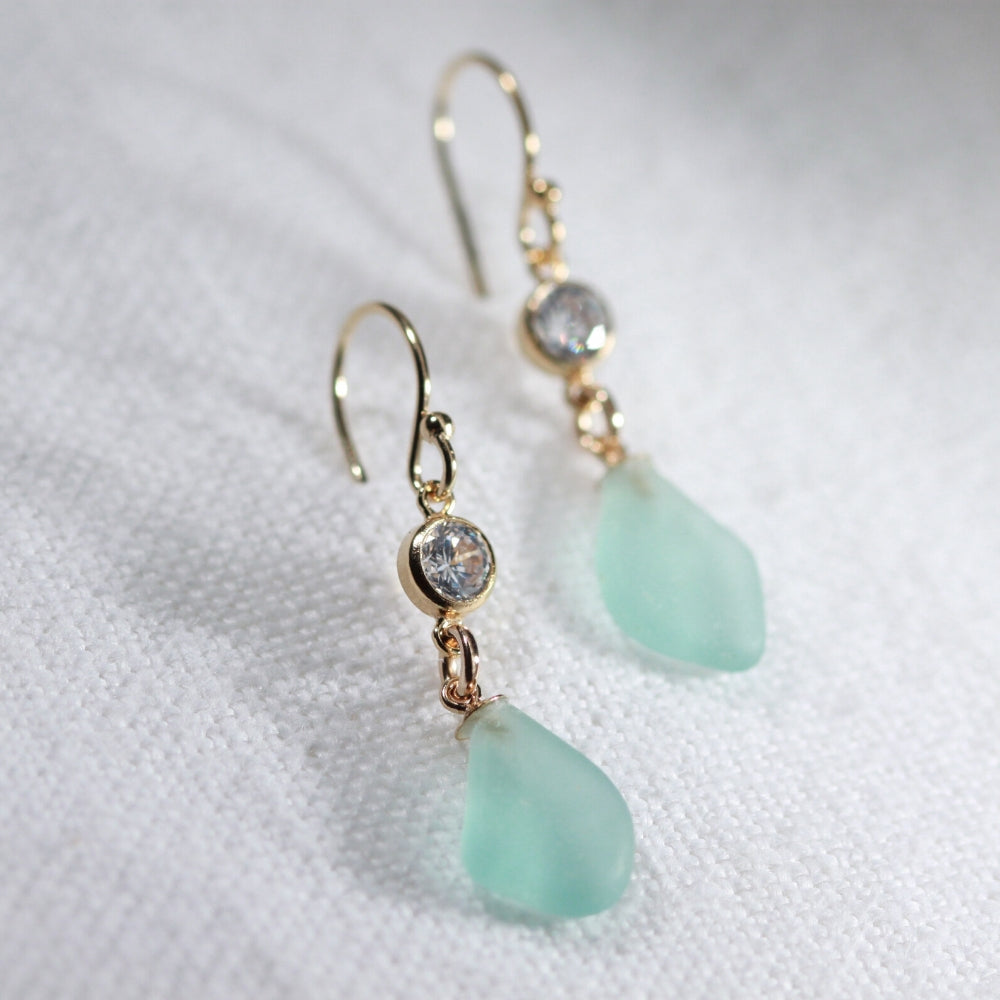 Aqua Sea Glass Earrings in 14 kt gold-filled hanging from a sparkly bezel set CZ