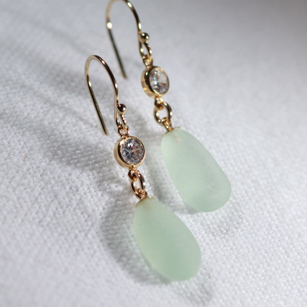 Sea foam green Sea Glass Earrings in 14 kt gold-filled hanging from a sparkly bezel set CZ