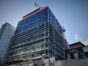 The International Apartments under construction. Scaffolding being removed using Advance Guardrail & Geda 200 Material Hoist