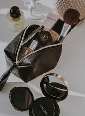 A purse exploding with beauty products
