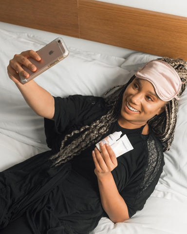 Lady lying on the bed taking a selfie with skincare products
