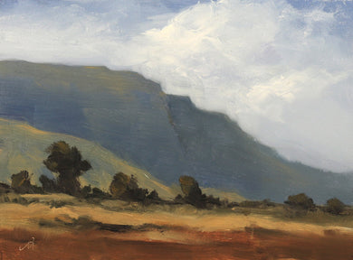 Landscape painting of huge mountain with some open field and a few trees in the foreground. Clouds in the sky suggest an approaching storm.