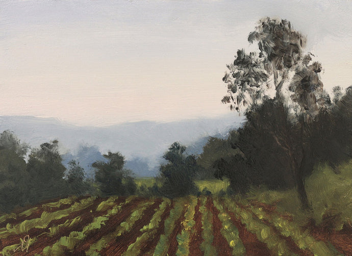Landscape painting of an evening at a farm with pale yellow and blue sky, blue distant mountains, dark trees and a green crop.