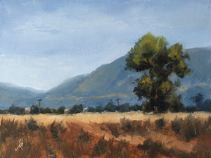 Morning time landscape painting with blue sky, distant mountains, a harvested field and a tall tree in the mid ground.